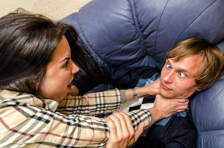 stifle: Office fight  Woman trying to stifle a man on the sofa