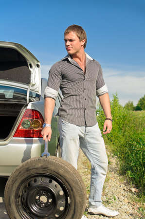Attractive male changing tires on the road photo