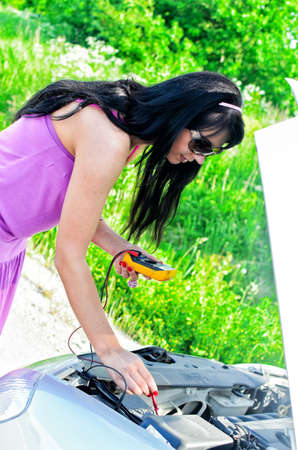 Woman controls lead�acid battery charge with voltmeter photo