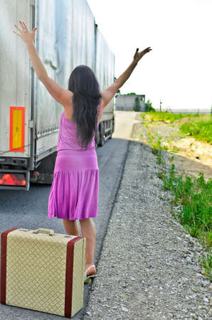 hitchhiking: Woman with suitcase hitchhiking a car Stock Photo