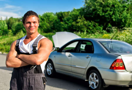 Handsome mechanic on a road near the broken car. photo
