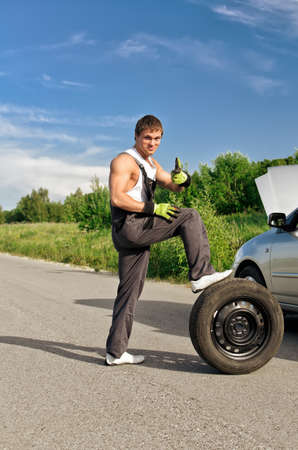 Handsome mechanic with a tire on a road photo