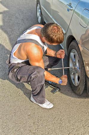 handtools: Mechanic fixing a tire on a road