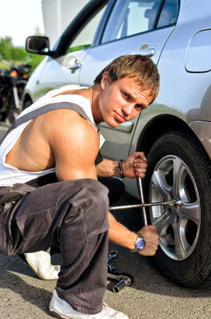 Mechanic fixing a tire on a road photo