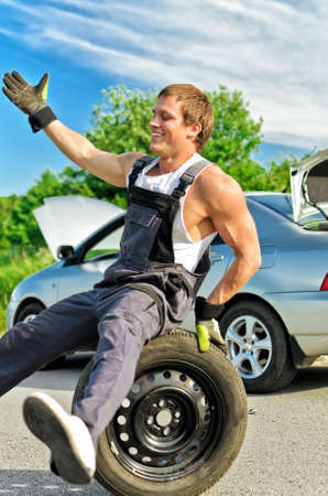 Portrait of laughing mechanic sitting on a tire on a road. photo