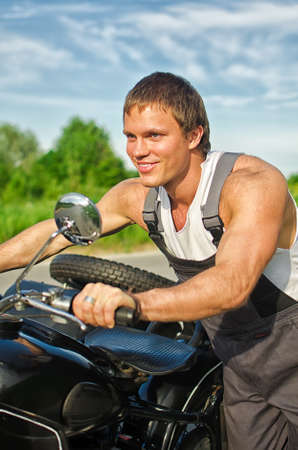 Portrait of handsome mechanic pushing a motorcycle photo