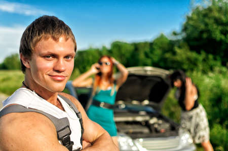 Portrait of handsome mechanic with two helpless women and broken car on background photo