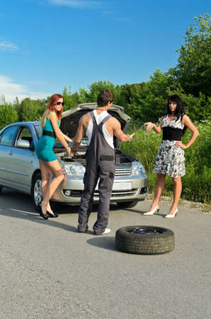Mechanic and two girls near the broken car on a road photo