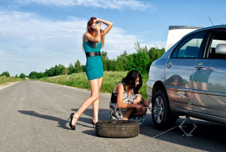 Two girls are fixing a changing a tire. photo