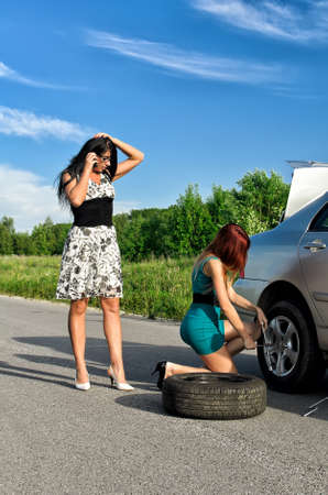 Two women are changing a tire on a road photo