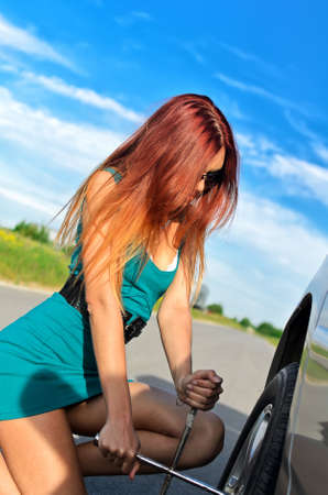 Portrait of a pretty girl changing broken tire on a road