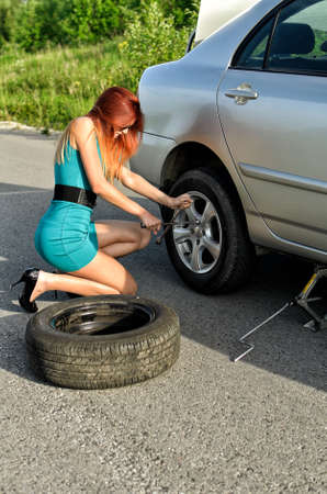 summer tire: Pretty girl is trying to change a tire on a road Stock Photo
