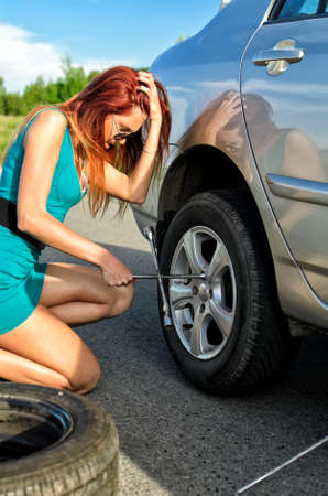 Pretty girl is trying to change a tire on a road Stock Photo - 14201239