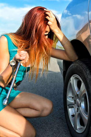 Pretty girl is trying to change a tire on a road Stock Photo - 14201243