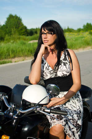 Portrait of a pretty woman on a retro motorcycle photo