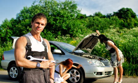 Portrait of a hadsome mechanic with two women on a background photo