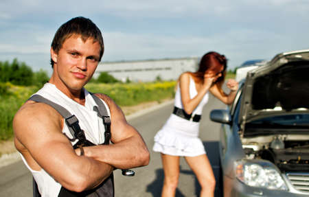 Portrait of a hadsome mechanic with a girl near broken car on a background photo