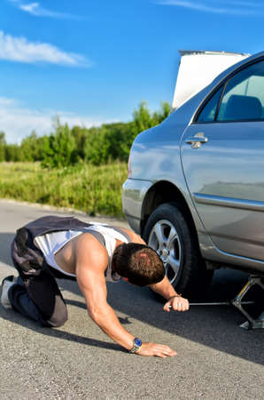 Mechanic sets a jack-screw under the car on a road Stock Photo - 14201230