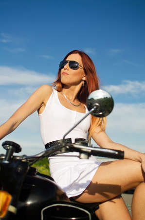 Sexy girl on a motorbike on a sky background photo