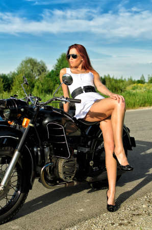 Sexy lady posing on a retro black motorcycle photo