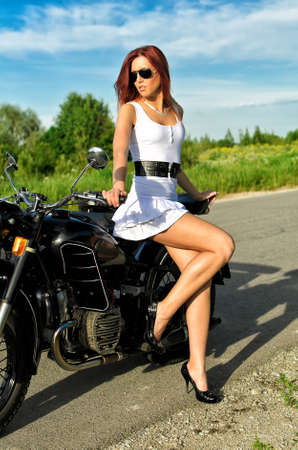 defiant: Sexy young woman posing near vintage motorbike Stock Photo