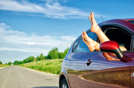 Womans legs out of the car window. Concept of carefree funny trip. photo