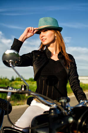 Portrait of a sexy lady in a hat sitting on motorcycle photo