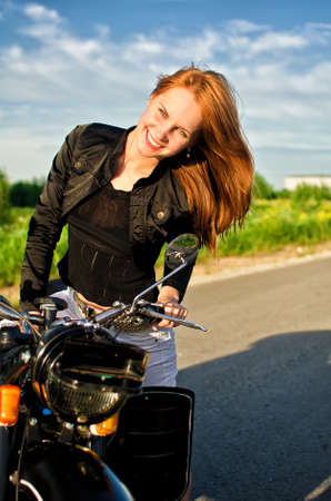 Smiling redhead girl on a motorbike on a road photo
