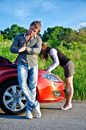 Man is waiting his girlfriend repairs a broken car photo