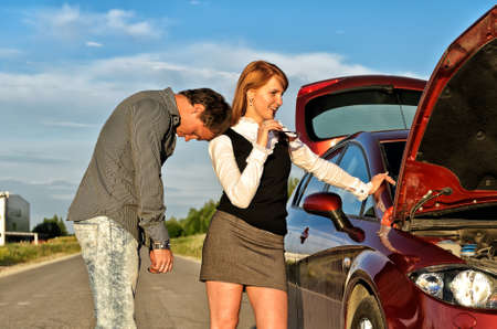 Tired man leaning to his gilfriend shoulder near broken car photo