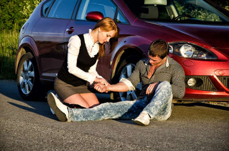 traffic accidents: Young girl masures mans pulse on a road. First aid Stock Photo
