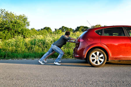 Man and woman pushing a broken car photo