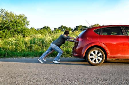 Man en vrouw het duwen van een kapotte auto