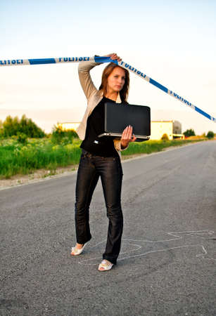 Young criminalist with laptop crossing police tape photo