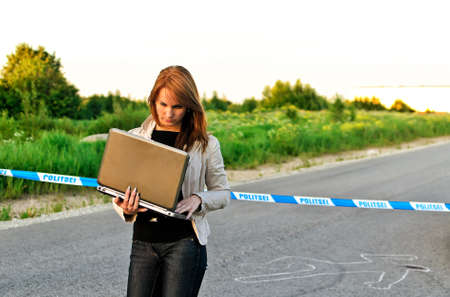 Young criminalist with laptop on a crime scene photo