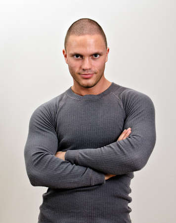Sporty male with arms folded. On grey background photo