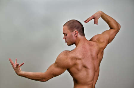 Muscular bodybuilder posing. On grey background. Stock Photo - 14265379