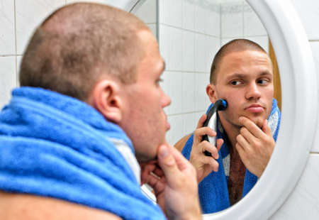 Male with towel shaving in bathroom in front of the mirror.  photo