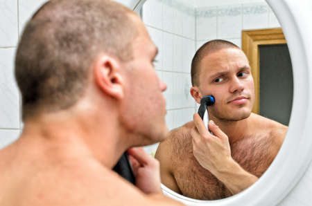 Male shaving in bathroom in front of the mirror.  photo