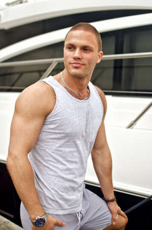 Attractive muscular male near the yacht photo