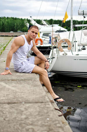 Attractive muscular male sitting near the yacht photo