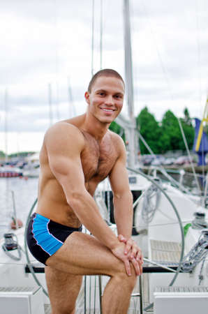 Muscular handsome sailor on his yacht. photo