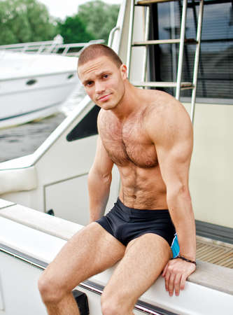 yachtsman: Muscular handsome sailor on his yacht