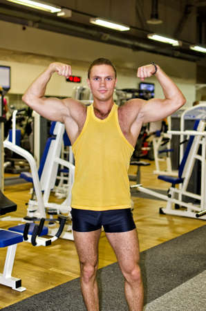 Handsome bodybuilder showing his muscular arms in gym Stock Photo - 14584036