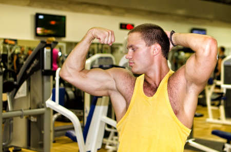 Handsome bodybuilder showing his muscular arms in gym Stock Photo - 14584034