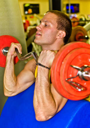 Portrait of handsome bodybuilder doing exercise in fitness club photo