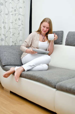 Woman with tablet pc on the sofa. photo