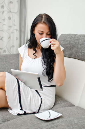 Brunette girl with tablet pc on the sofa. photo