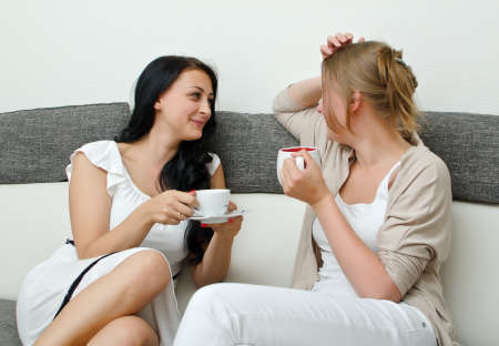 chat room: Two women friends chatting over coffee at home Stock Photo