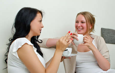 Two women friends chatting over coffee at home photo